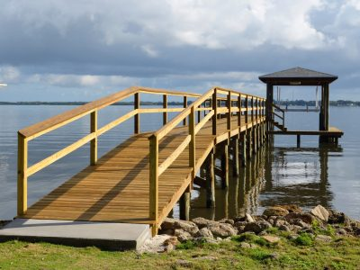 Custom Boat Dock with boat lift, double sided railing and concrete landing at the beginning of the walkway