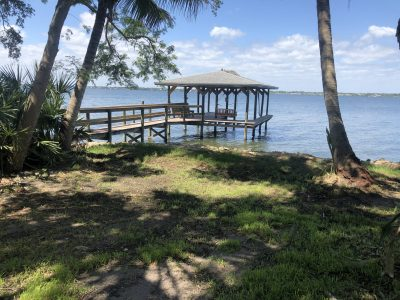 Custom boat dock and boat slip with roof, full dock length wood railing to match, Brevard County FL